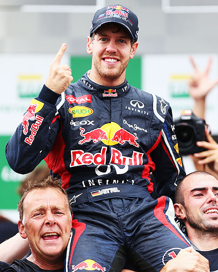 Sebastian Vettel celebrates with teammates on the podium after finishing in sixth position and clinching his third consecutive drivers world championship on Sunday
