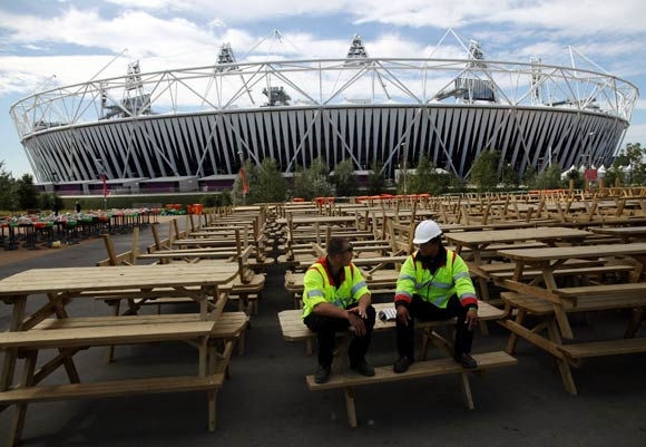 Workmen take a break on a row of upturned benches outside the Olympic Stadium in Stratford, East London