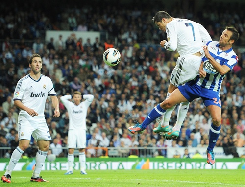 Cristiano Ronaldo (left) of Real Madrid scores past Carlos Marchena of Deportivo La   Coruna