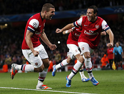 Arsenal's Lukas Podolski (left) celebrates after scoring against Olympiakos Piraeus during their Champions League match on Wednesday
