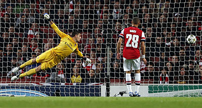 Arsenal goalkeeper Vito Mannone (left) dives as Olympiakos Piraeus' Kostas Mitroglou (not pictured) scores during their Champions League match on Wednesday