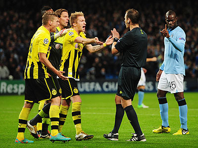 Roman Weidenfeller of Borussia Dortmund and his teammates protest to referee Pavel Kralovec after he awarded a penalty to Manchester City as Balotelli gestures during their Champions League match on Wednesday