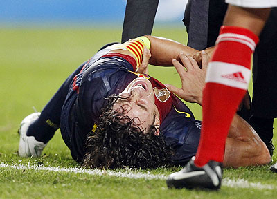Barcelona's Carles Puyol grimaces after falling and sustaining an injury during their Champions League match against Benfica on Tuesday