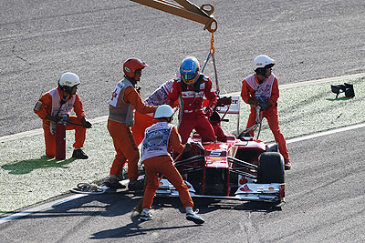 Ferrari's Fernando Alonso is helped from his car by race marshalls after spinning out at the first corner at the start of the Japanese Formula One Grand Prix on Sunday