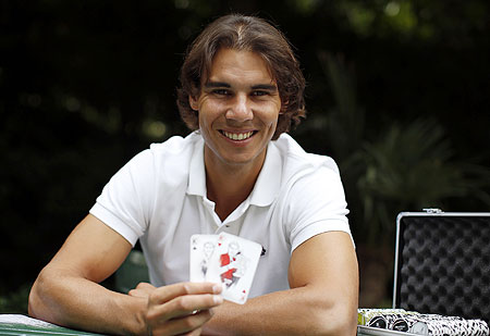 Rafael Nadal hols up playing cards depicting some of his 11 Grand Slam victories