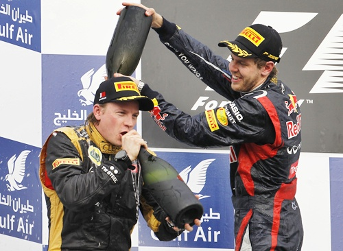 Sebastian Vettel pours champagne on second placed Lotus F1 Formula One driver Kimi Raikkonen