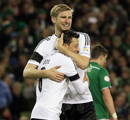 Germany's Per Mertesacker congratulates Mesut Ozil (front) after he scored against Ireland