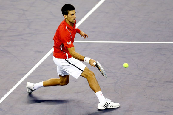 Novak Djokovic of Serbia returns a shot to Tommy Haas of Germany