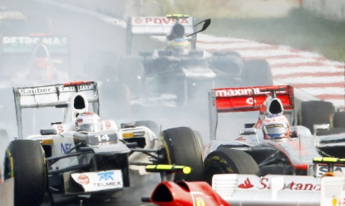 Sauber Formula One driver Kamui Kobayashi (left) of Japan collides with McLaren driver Jenson Button