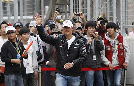 Mercedes driver Michael Schumacher waves to fans before an autograph signing session at the Korea International Circuit in Yeongam