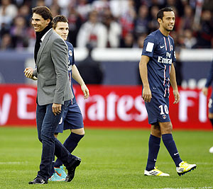Rafael Nadal (left) walks past Paris St Germain's Nene (right) and Kevin Gameiro (centre) before the French Ligue 1 soccer match between Paris Saint Germain and Reims at the Parc des Princes stadium in Paris on Saturday