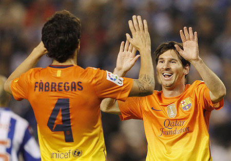 Barcelona's Lionel Messi (right) celebrates with teammate Cesc Fabregas aftr scoring against Deportivo Coruna