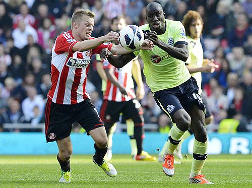 Sunderland's Sebastian Larsson (left) challenges Newcastle United's Demba Ba