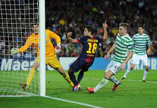 Jordi Alba (C) of Barcelona celebrates scoring in between Goalkeeper Fraser Forster (L) and James Forrest of Celtic FC after scoring his sides winning goal
