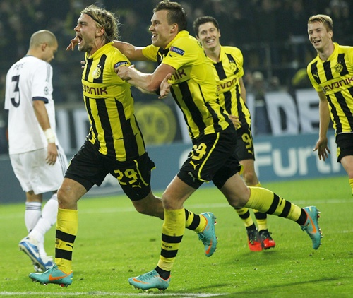 Borussia Dortmund's Marcel Schmelzer (centre) celebrates with his teammates   Kevin Grosskreutz and Robert Lewandowski after scoring a goal against Real   Madrid