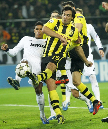 Real Madrid's Raphael Varane (left) fights for the ball with Borussia   Dortmund's Mats Hummels