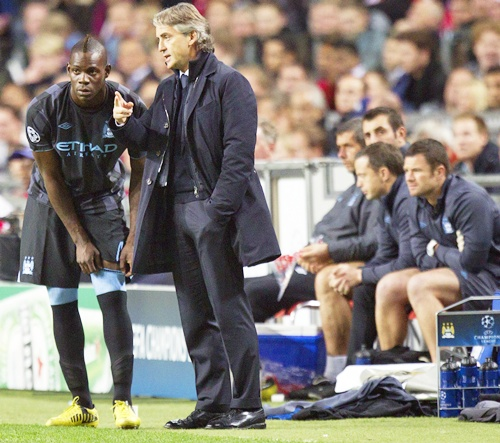 Manchester City's manager Roberto Mancini speaks to Mario Balotelli (left)