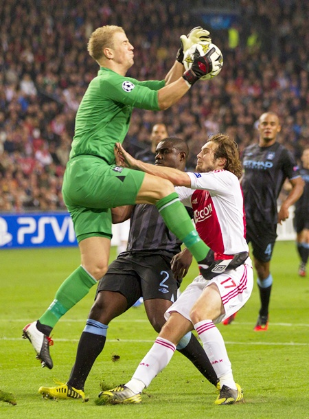 Daley Blind of Ajax Amsterdam (right) fights for the ball with Manchester City's goalkeeper Joe Hart