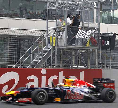 Gagan Narang waves the flag as Red Bull driver Sebastian Vettel crosses the line to win the Indian F1 Grand Prix