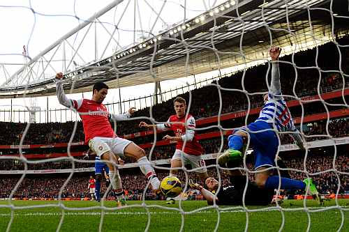 Mikel Arteta of Arsenal pokes the ball past Ryan Nelsen of QPR to score the opening goal during the Barclays Premier League match between Arsenal and QPR
