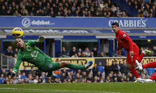 Everton's Tim Howard fails to keep out a header by Liverpool's Luis Suarez during their English Premier League soccer match at Goodison Park