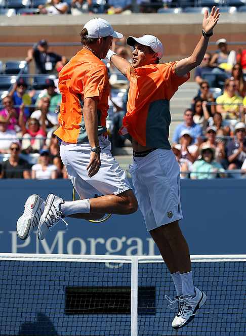 Bob Bryan (L) and Mike Bryan (R) celebrate match point with a chest bump against Leander Paes and Radek Stepanek