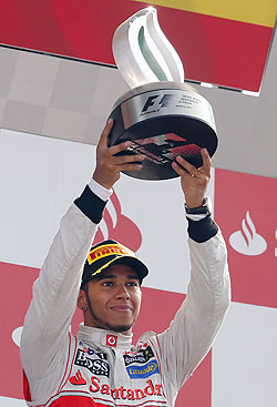 McLaren Formula One driver Lewis Hamilton of Britain holds up the trophy on the podium after winning the Italian F1 Grand Prix at the Monza circuit on Sunday