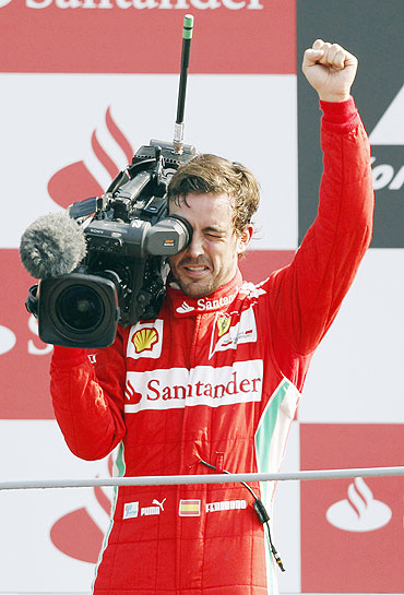 Ferrari's Fernando Alonso films supporters on the podium as he celebrates his third place finish in the Italian F1 Grand Prix at the Monza circuit on Sunday