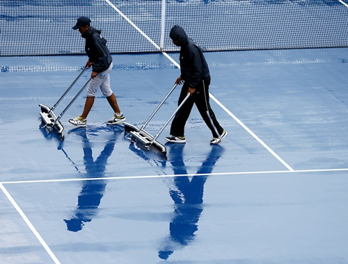 Grounds crew dry the court after rain suspened action
