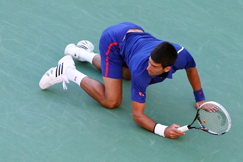 Novak Djokovic of Serbia drops to the floor