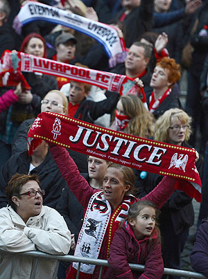 Members of the crowd react during a vigil at St George's Hall in Liverpool
