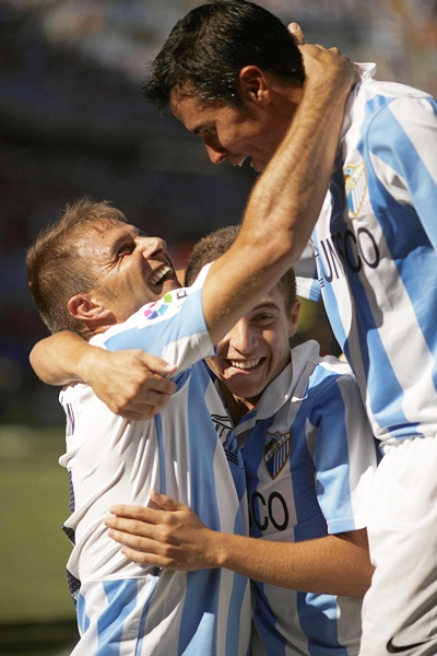 Malaga's Joaquin Sanchez (left) is congratulated by his teammates Francisco Portillo   (centre) and Javier Saviola
