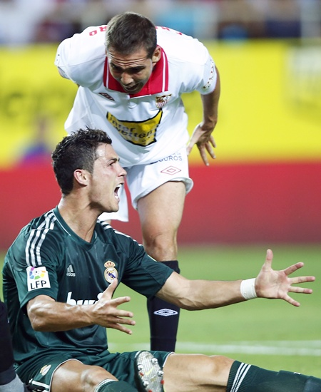 Real Madrid's Cristiano Ronaldo (bottom) reacts next to Sevilla's Fernando Navarro