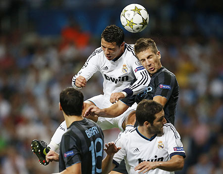 Real Madrid's Cristiano Ronaldo (top left) goes for a header as he is challenged by Manchester City's Matija Nastasic