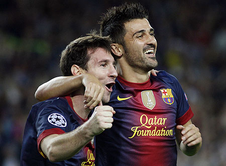 Lionel Messi celebrates with teammate David Villa after scoring