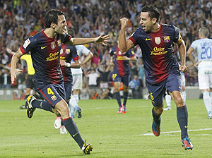 Barcelona's Xavi Hernandez (right) celebrates with teammate Cesc Fabregas after scoring against Granada during their La Liga match at Camp Nou on Saturday