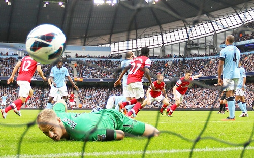 Joe Hart of Manchester City looks on as Laurent Koscielny of Arsenal turns to celebrate after scoring