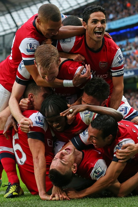 Laurent Koscielny of Arsenal is mobbed by his teammates after scoring