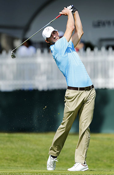 US Olympian Michael Phelps hits his tee shot on the second hole during the Captains and Celebrity Scramble at the 39th Ryder Cup golf matches at the Medinah Country Club in Medinah, Illinois