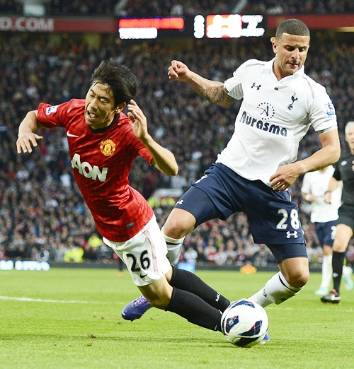 Manchester United's Shinji Kagawa (left) is challenged by Tottenham Hotspur's Kyle   Walker