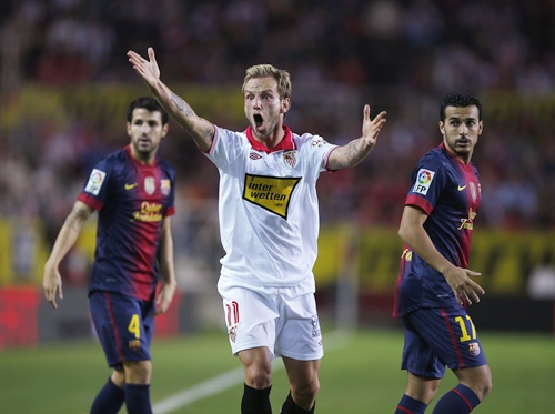 Sevilla's Ivan Rakitic (centre) reacts next to Barcelona's Cesc Fabregas (left) and Pedro Rodriguez