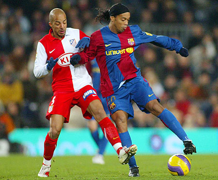 Ronaldinho of Barcelona and Luccin of Atletico Madrid in action during their match at the Camp Nou stadium in Barcelona in December 2006
