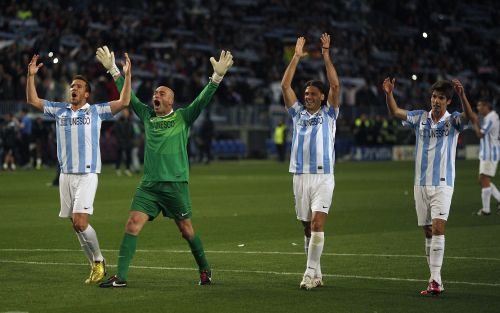 Malaga's players celebrate their victory over Porto