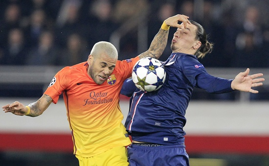 Paris St Germain's Zlatan Ibrahimovic (right) challenges Barcelona's Daniel Alves