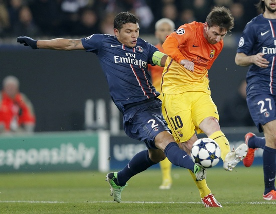 Paris St Germain's Thiago Silva (left) challenges Barcelona's Lionnel Messi