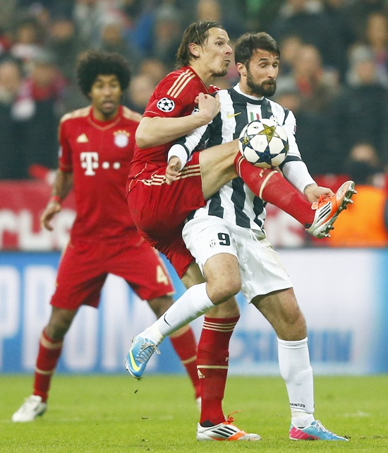 Daniel van Buyten (left) of Bayern Munich challenges Mirko Vucinic of Juventus