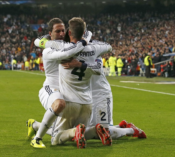 Real Madrid's Gonzalo Higuain (left) celebrates his goal against Galatasaray with captain Sergio Ramos ( centre ) and Raphael Varane