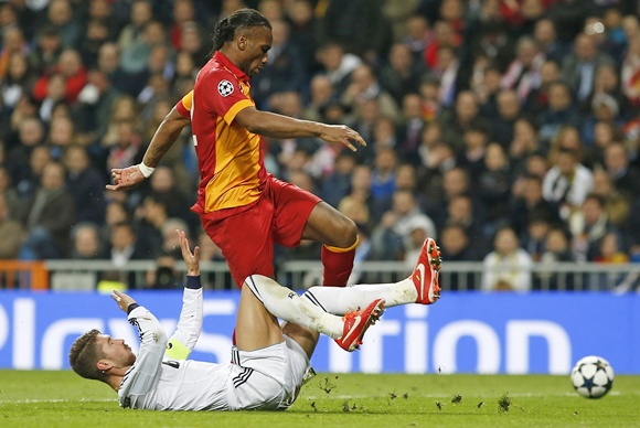 Real Madrid's Sergio Ramos (left) fights for the ball with Galatasaray's Didier Drogba