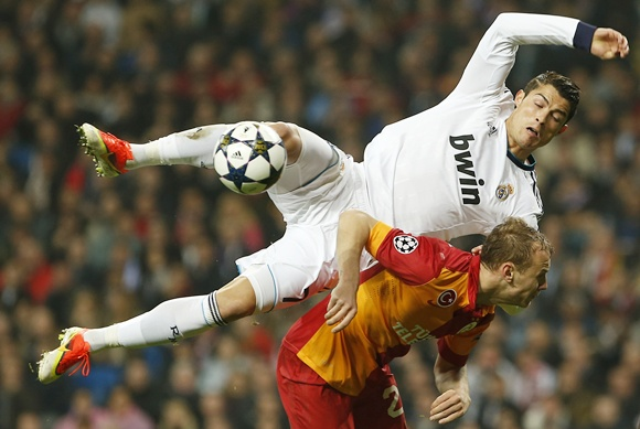 Real Madrid's Cristiano Ronaldo disputs a ball over Galatasaray's Semih Kaya