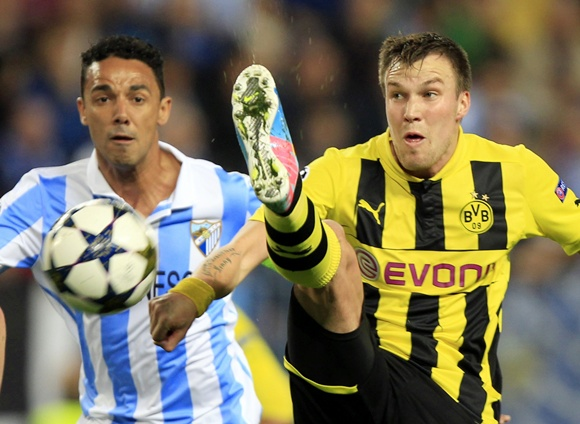 Borussia Dortmund's Kevin Grosskreutz (right) goes for the ball against Malaga's Weligton Robson